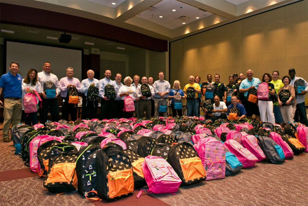 group picture with 650 backpacks